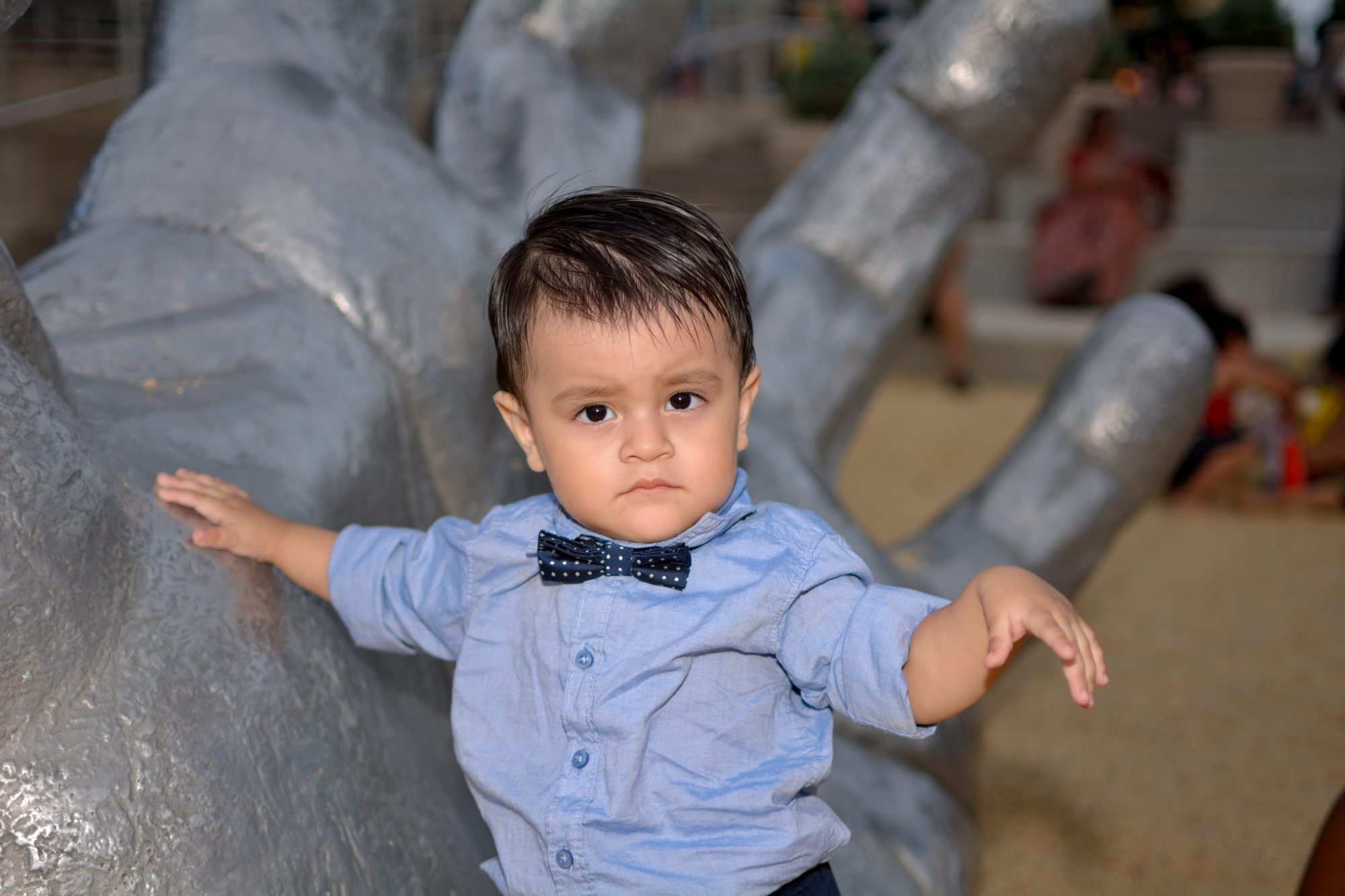 tomas hric photography's stunning family photographer portrait of handsome little boy in front of a giant hand national harbor